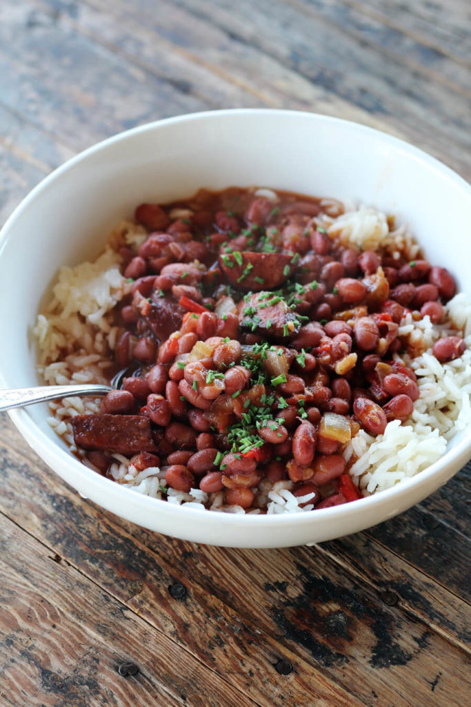 A white bowl with rice, red beans, smoked sausage