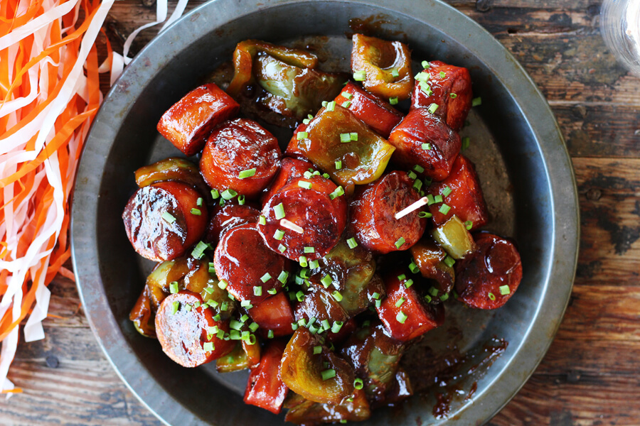 vintage metal plate with saucy sausage and green peppers sprinkled with fresh, chopped chives