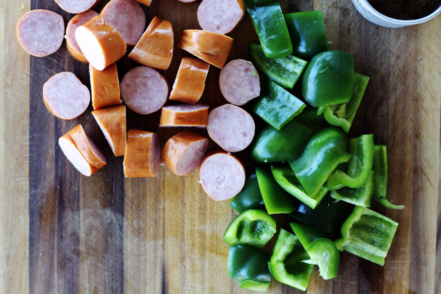 sliced sausage and green bell pepper on a cutting board
