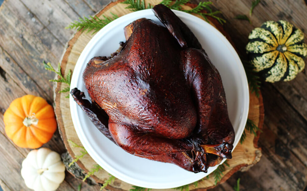 Cider Brined Smoked Turkey on a white platter next to natural elements