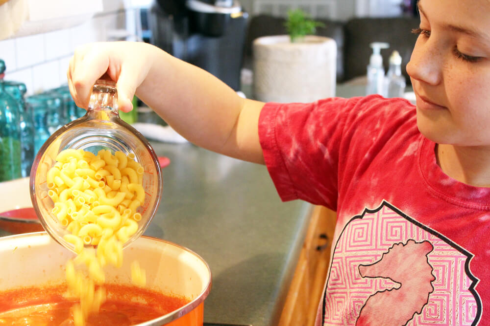 A girl cooking in the ktichen, pouring macaroni pasta into a pot.