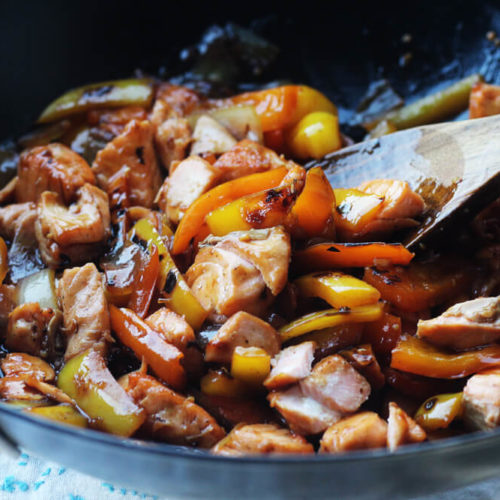 a wok with stir fry salmon, bell peppers, onions